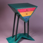 "Triangle Cabinet: 2006 Birch Plywood, Curly Maple, Dye, Splatter Paint about 28"" tall, 20"" wide, 12"" deep $1200"
